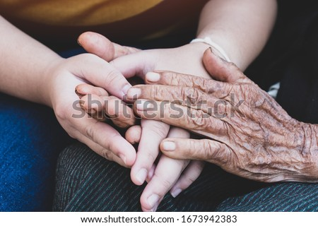 Young grandchildren's holding older grandmother hands feel with support together, wrinkled skin with feeling take care. World Kindness Day, Adult day center Relationship of Family mother day concept Foto stock ©