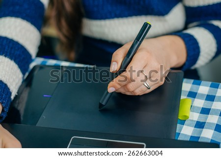 Young graphic designer working on laptop using tablet at home.