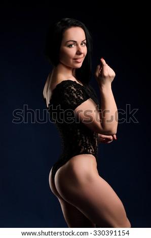 young green-eyed brunette woman in black leotard on dark blue studio background #330391154