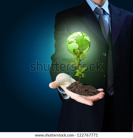 Young green plant in the hand of a businessman