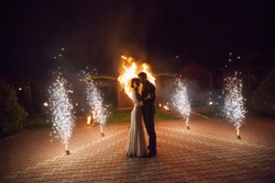 Young groom and bride with two burning hearts fireshow at night, wedding or marriage concept.