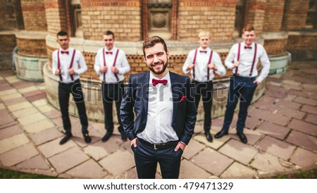 Young groom and his funny friends groomsman posing for camera. Group of young men with bow tie. Cheerful friends. friends outdoors. Wedding day.
