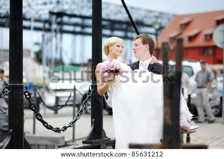 Young groom carrying his beautiful bride