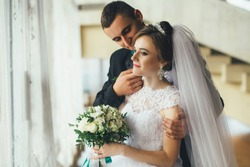 Young groom hugs bride tender standing in the hall before a window