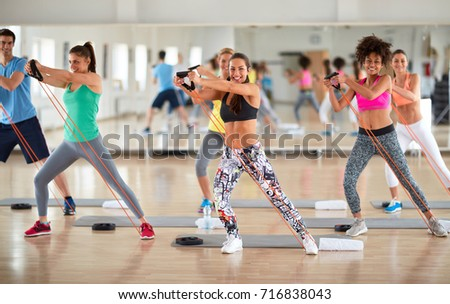 Young group of exercisers doing exercises with resistant rubber in fitness class #716838043