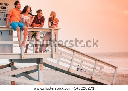 Young Group of Friends at the Beach at Sunset with American Flags