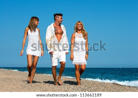 Young group of friends dressed in white wandering along sunny beach.