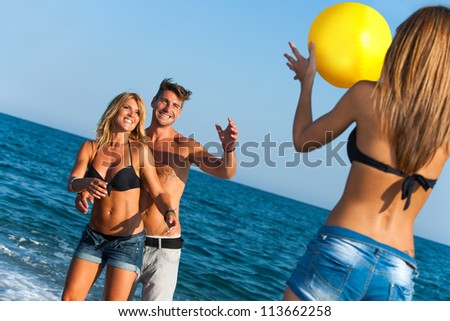 Young group of friends having fun with ball game on beach.