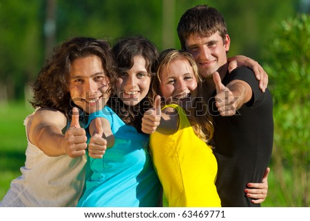 Young group of happy friends showing thumbs up sign together outdoor in the park