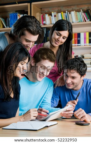 Young group of happy students studying and working together in a college library