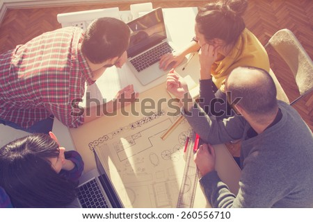 Young group of people/architects discussing business plans.