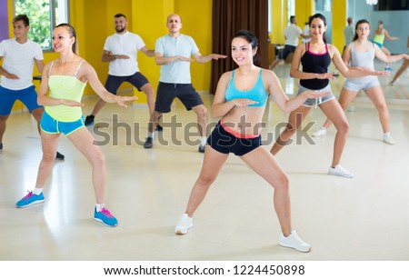 Young group of people are learning zumba movements in dance class. #1224450898