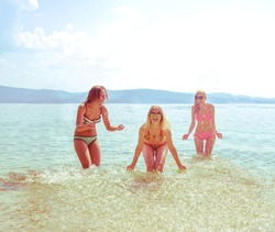 young group of people dabble in ocean at sunset. Team of adult girl jump in water on summer beach on blue sky with clouds. Water splash. holiday at summertime.