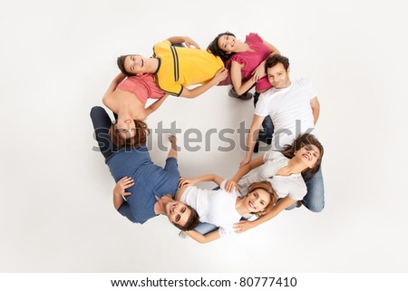 young group of people standing in a circle holding each other on their backs