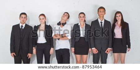 Young group of teenage business people with one young man standing out of the crowd. - stock photo