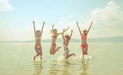 young group of women jumping in ocean at sunset.Team of adult girls jumping in water on summer beach on blue sky with clouds.Water splash Hair fly in air.Empty space for inscription. enjoy summertime