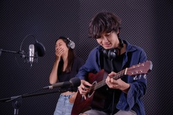 young guitarist and vocalist in music studio record room