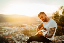 Young guitarist playing acoustic guitar and looking to sunset.Searching inspiration.Music creator.New artist.Musical talent.Handsome guitarist enjoying sunset and playing acoustic guitar.