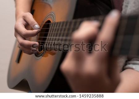 Young guitarist playing classical guitar with both hands. Shallow depth of field.