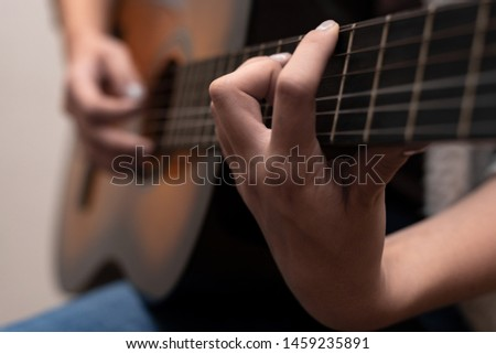 Young guitarist playing guitar with both hands. Shallow depth of field.