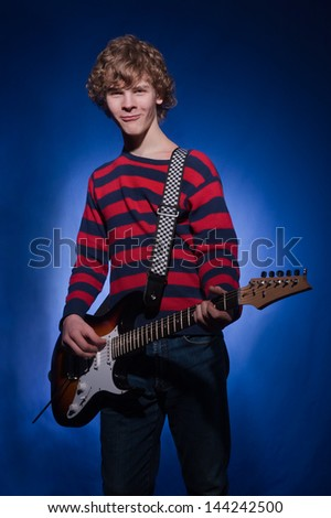 young guitarist plays the electric guitar Blues on a dark blue  background
