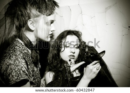 Young gupsy woman playing with black cat against grungy wall - stock photo