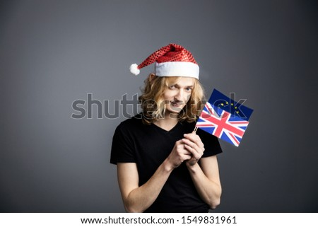 Young guy an attractive guy with long blonde hair in the form of a Christmas elf in a Santa Claus hat  holding EU and UK flags  on a gray background