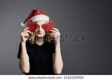 Young guy an attractive guy with long blonde hair in the form of a Christmas elf in a Santa Claus hat  closed his eyes with red hearts on a gray background.