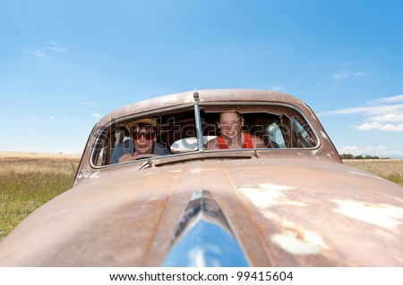 Young guy and girl in a rusty old car