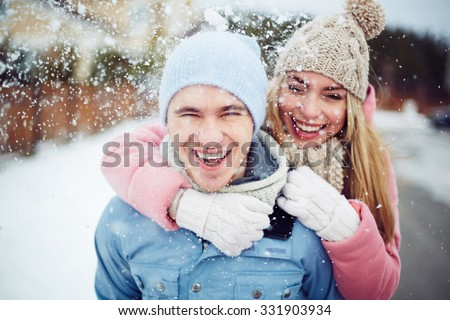 Young guy and girl in winterwear enjoying snowfall #331903934