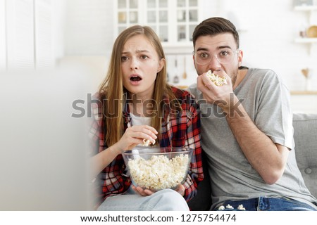 Young guy and girl looking at TV screen holding popcorn bowl and eating, showing great amazement, fear and disappointment, being very attentive to what is going on