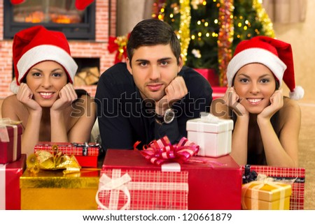 young guy and two beautiful twin girls enjoy in Christmas night