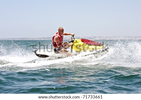 Young guy cruising on the atlantic ocean on a jet ski