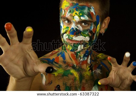 Young guy face, body and hands painted with colored ink - stock photo
