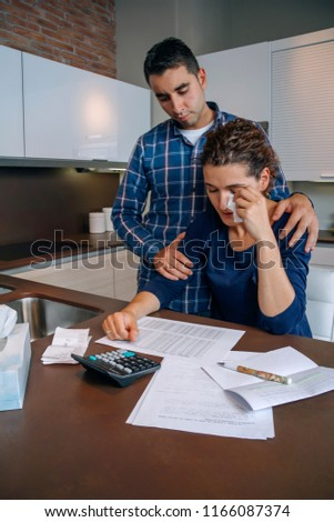Young guy friend gives solace to desperate unemployed woman crying by her debts. Financial problems concept.