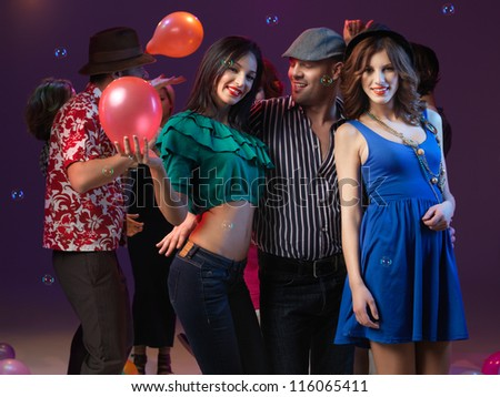 young guy holding and dancing with two girls who smile and pose for the camera, with balloons, bubbles and poeple dancing in teh background