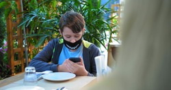 young guy in black designed face mask types on smartphone sitting at restaurant table on terrace and mom hair on foreground