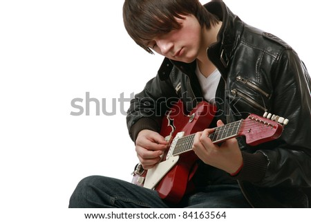 Young guy in leather jacket playing electric guitar
