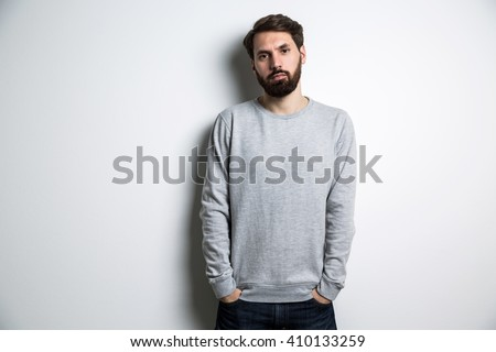 Young guy in long sleeved sweatshirt on light grey background