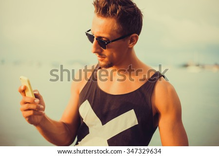young guy in sunglasses t-shirt talking on the smartphone to respond to messages texting working abroad,freelance working,typing online,social networks,periscope,wi-fi ,hand watch ,phone 6s #347329634