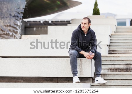 Young guy is a tired athlete guy sitting on the curb after a grueling cardio workout outside on a warm summer morning. The concept of regular workouts and a healthy lifestyle. Copyspace