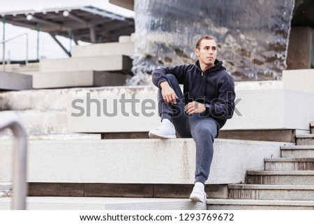 Young guy is a tired fitness blogger guy sitting on the curb after a grueling cardio workout outside on a warm summer morning. The concept of regular workouts and a healthy lifestyle. Copyspace #1293769672