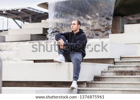 Young guy is a tired triathlete guy sitting on the curb after a grueling cardio workout outside on a warm summer morning. The concept of regular workouts and a healthy lifestyle. Copyspace