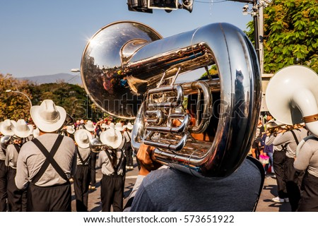 Young guy is playing tuba during parade show with the group in a sunny day.