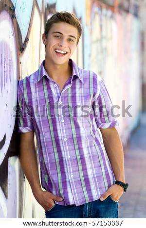 stock photo : Young guy leaning on graffiti wall