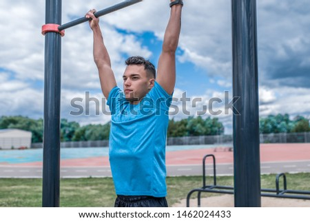 young guy, man sports athlete, in summer in city on sports ground, pulls up on bar, workout fitness, workout healthy lifestyle. Sportswear, strength and endurance, motivation