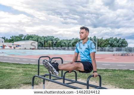 young guy, man sports athlete, summer city sports ground, training abdominal muscles, lifting legs, exercise area, fitness , workout healthy lifestyle. Sportswear, strength and endurance, motivation