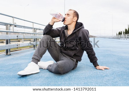 Young guy personal trainer in a gray suit drinking water from his bottle after a fat burning morning street workout. Concept of water balance replenishment during workouts