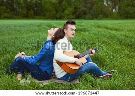 young guy playing guitar for his girlfriend