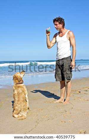 Young guy playing with his dog at the beach